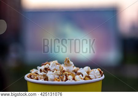 A Glass Of Caramel Popcorn On A Blurry Screen Background. Cozy Evening Viewing Of A Movie Or Tv Seri