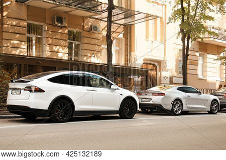 Kiev, Ukraine - May 22, 2021: White Electric Car Tesla Model X And Gray American Muscle Car Chevrole