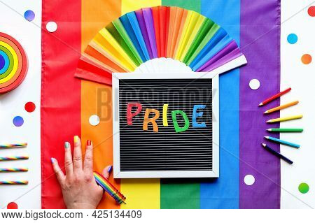 Rainbow Lgbt Flag Background With Frames, Fan, Pencils And Ribbons. Hand With Painted Nails.text Pri