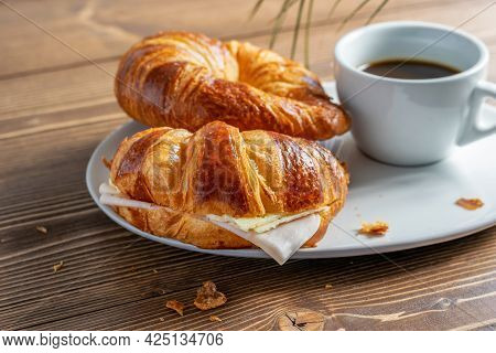 Two French Croissants With Ham And Cheese And A Cup Of Black Coffee On The White Plate. Wooden Table