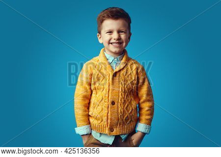 Kid Smiling While Holding Hands In Pockets, Isolated Over Blue Background
