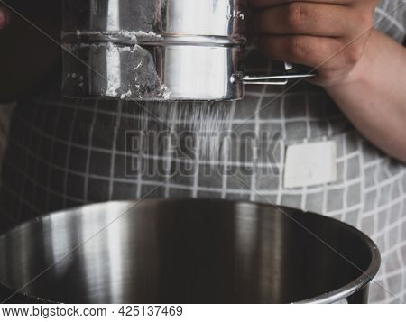 The Girl's Hand Holds A Metal Sifter Of Flour, Flour Is Sprinkled Through A Sieve. Sifting Flour. Pr