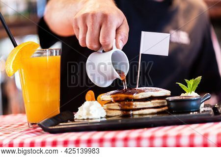 Sweet pancakes dripped with maple syrup served in american restaurant