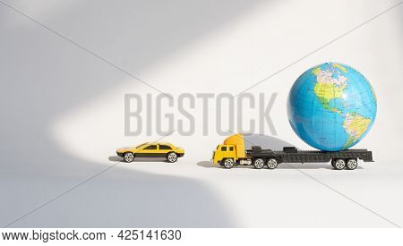 The Globe Is Transported In A Toy Truck, Accompanied By Security In A Passenger Car. The Concept Of