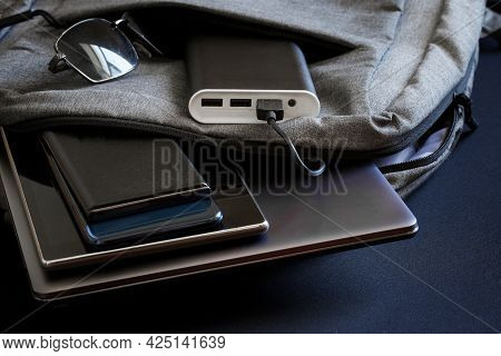Portable Charger - Power Bank Lies In Backpack Along With  Gadgets - Smartphones, Tablet And Slim Fa