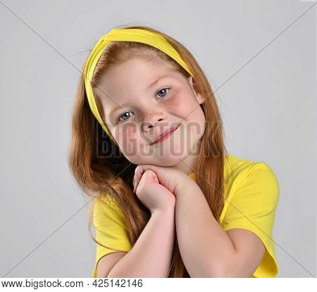 Charming Red-haired Girl Child With Folded Hands Under Cheek Studio Face Portrait Shot. Female Kid W