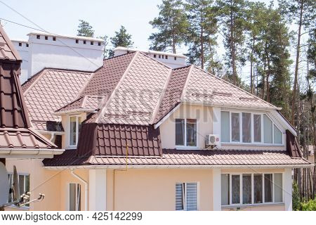 Roof On Residential Property With New Brown Corrugated Metal Roof Tiles. Modern Metal Roof. Metal Ro