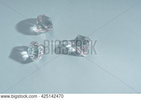 Three Shiny Brilliants Stone On Blue Background