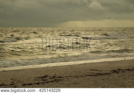 Thick Storm Clouds Fill The Sky Over The Gulf Of Mexico In Bonita Springs, Florida, As Waves Crash O