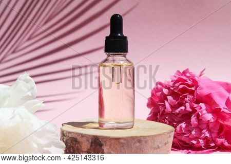 Bottle Of Cosmetic Essential Oil With Dropper On A Wood Cut With Peony Flowers And Palm Leaf Shadow.