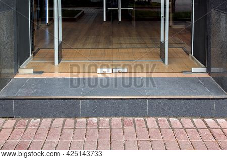 A Threshold With A Step At The Entrance To The Store With A Tempered Glass Door In The Doorway Tiled