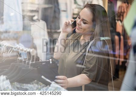 Happy Plus Size Beautiful Woman Shopaholic Choosing Clothes At Store Talking Smartphone
