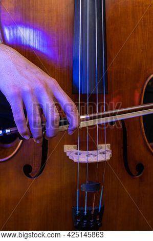 Detail Of A Hand Holding A Music Bow To Play A Cello And To Bring Out The Sound With Selective Focus