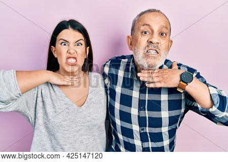 Hispanic father and daughter wearing casual clothes cutting throat with hand as knife, threaten aggression with furious violence