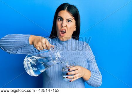 Beautiful brunette woman pouring water in glass in shock face, looking skeptical and sarcastic, surprised with open mouth