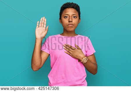 Young african american woman wearing casual clothes swearing with hand on chest and open palm, making a loyalty promise oath