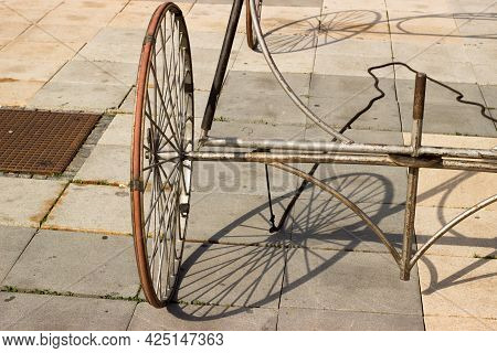 The Wheel Of A Cart And Its Shadow On A Paved Sidewalk