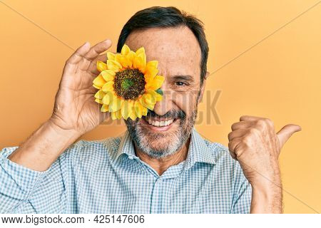 Middle age hispanic man holding sunflower over eye pointing thumb up to the side smiling happy with open mouth