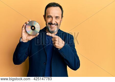 Middle age hispanic man holding compact disc smiling happy pointing with hand and finger