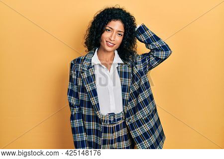 Young latin girl wearing business clothes confuse and wonder about question. uncertain with doubt, thinking with hand on head. pensive concept.