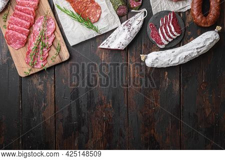 Variety Of Dry Cured  Chorizo, Fuet And Other Sausages Cut In Slices With Herbs On Dark Wooden Backg