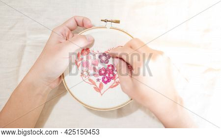Female Hand Holding Wood Embroidery Frame And Needle Working On Flower Pattern Stitching In A Proces
