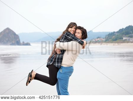 Biracial Young Man Lifting His Girlfriend Up In Arms While  On Beach Together Near Ocean