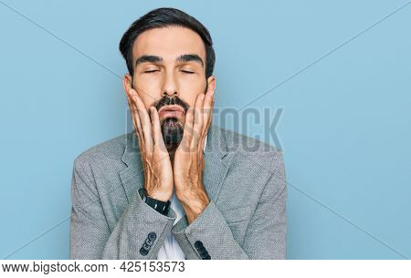 Young hispanic man wearing business clothes tired hands covering face, depression and sadness, upset and irritated for problem