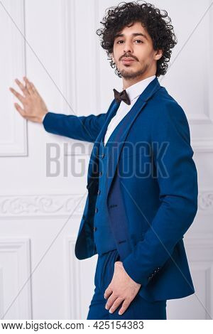 Men's style. Good-looking handsome man in elegant blue suit and a bow-tie poses in white classic apartments.