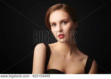 Portrait of a beautiful elegant girl on a black background. Evening look. Beauty and makeup.