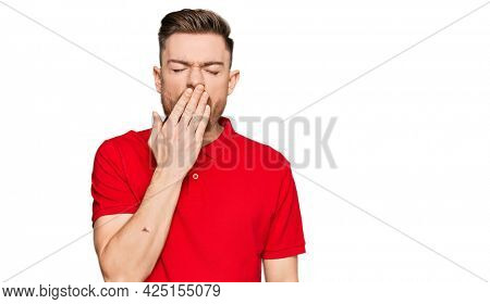 Young redhead man wearing casual clothes bored yawning tired covering mouth with hand. restless and sleepiness.
