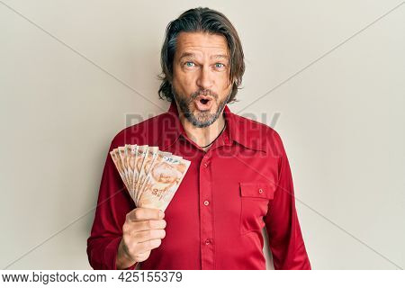 Middle age handsome man holding 50 turkish lira banknotes scared and amazed with open mouth for surprise, disbelief face