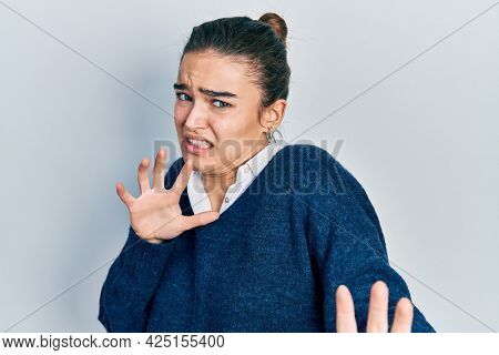 Young caucasian girl wearing casual clothes disgusted expression, displeased and fearful doing disgust face because aversion reaction. with hands raised