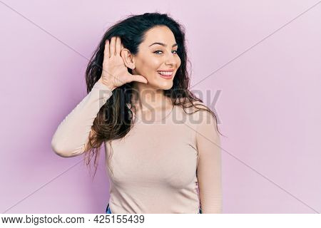 Young hispanic woman wearing casual clothes smiling with hand over ear listening and hearing to rumor or gossip. deafness concept.