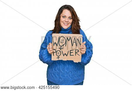Young plus size woman holding woman power banner looking positive and happy standing and smiling with a confident smile showing teeth