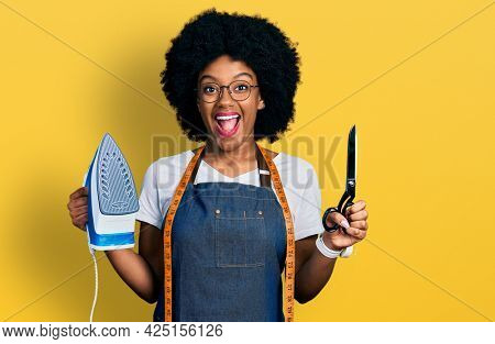 Young african american woman dressmaker designer wearing atelier apron holding iron and scissors celebrating crazy and amazed for success with open eyes screaming excited.