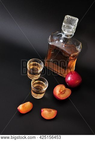 Homemade Plum Liqueur, Glass Bottle, Two Glasses And Sliced Ripe Fruits On A Black Background.