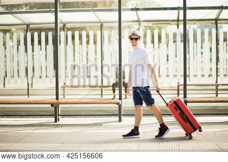 Handsome Young Arab Tourist Man With A Beard In Sunglasses Rolling Red Suitcase At Railway Station.