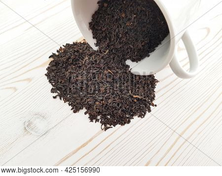 An Inverted White Cup With Scattered Black Tea On A Light Background With A Wooden Texture.