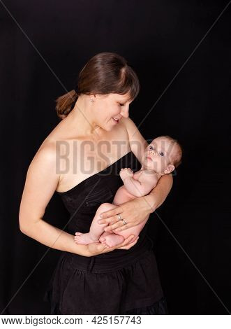 New Mom Spends Quality Time With Baby Boy. Joyful Mommy Carrying Baby In Arms Standing At Home. Mom