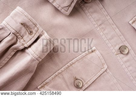 Elements Of Tailoring A Denim Beige Shirt Close-up. Pockets, Buttons, And Sleeves On A Denim Shirt.