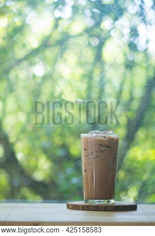 A Glass Of Iced Mocha Coffee Against Nature Background On Wooden Table