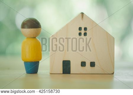 Wooden Figurines Of People Stand Near The House On A Nature Background. Search For A New Home And Re