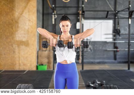 Woman During Training In The Gym. She Does A Dumbbell Exercise. Front View.