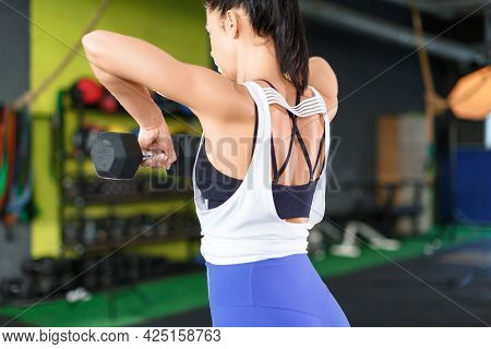 Woman During Training In The Gym. She Does A Dumbbell Exercise.