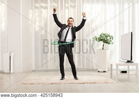 Full length portrait of a young businessman spinning a hula hoop inside a modern room