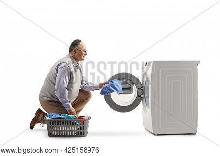 Mature man kneeling and loading a washing machine isolated on white background