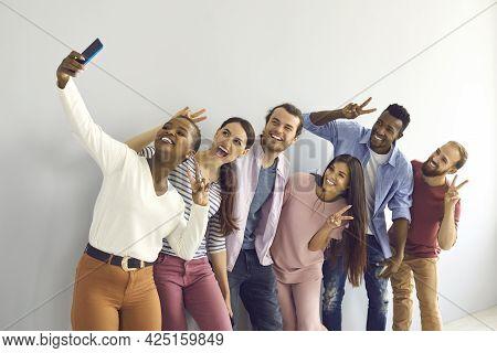Group Of Smiling Multinational Students Or Friends Showing V-sign Gestures Making Selfie.
