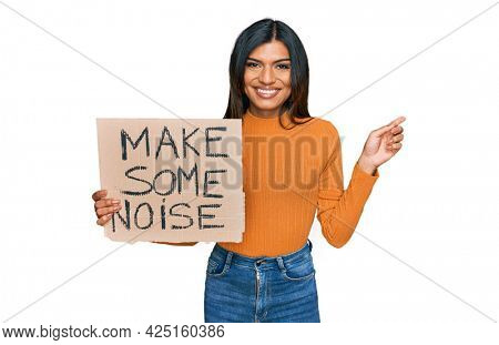 Young latin transsexual transgender woman holding make some noise banner smiling happy pointing with hand and finger to the side