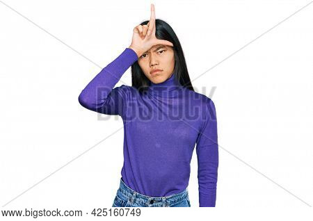 Beautiful young asian woman wearing casual clothes making fun of people with fingers on forehead doing loser gesture mocking and insulting.